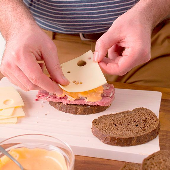 person laying slices of bread with cheese, meat, sauerkraut and sauce