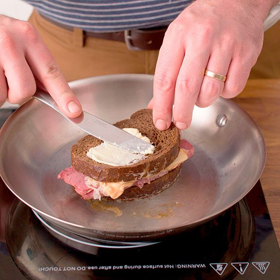 person toasting their assembled reuben on the stovetop while buttering the top-facing side