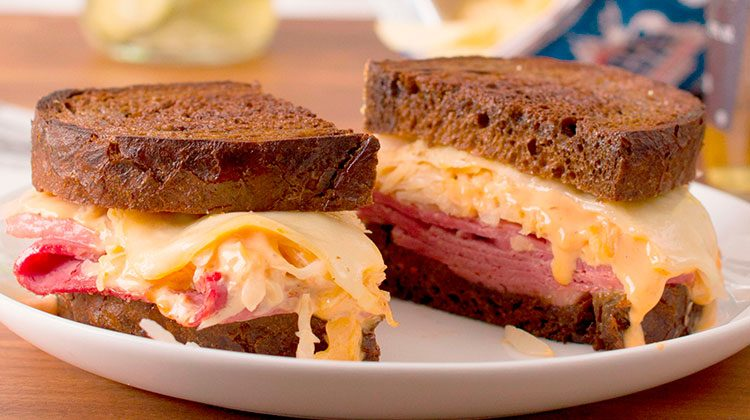Reuben sandwich cut in half sitting on a plate with gooey cheese pouring over its sides