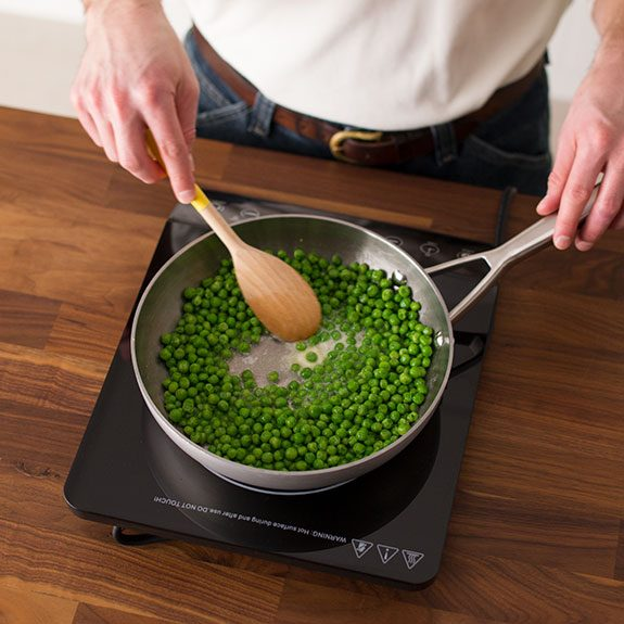 Person stirring peas in a skillet with a wooden spoon