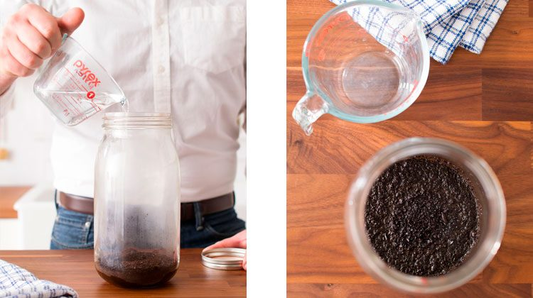 Coffee grinds at the bottom of a mason jar with hot water being poured over it