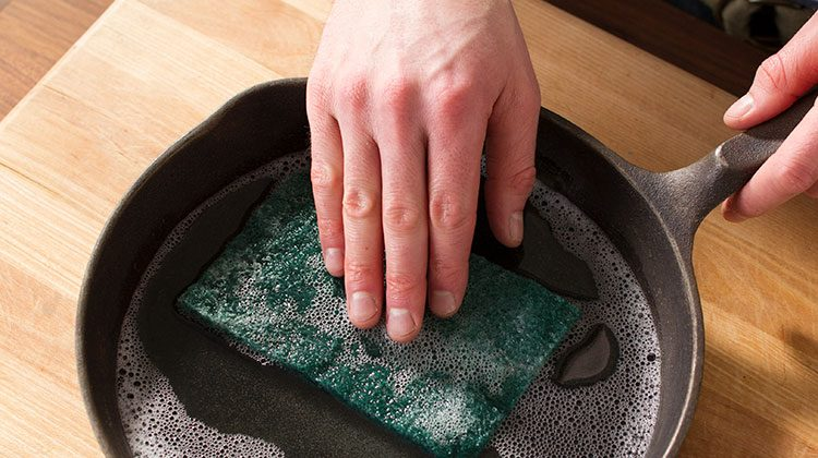 A hand runs a green sponge over the inside of a cast iron skillet filled with soapy water