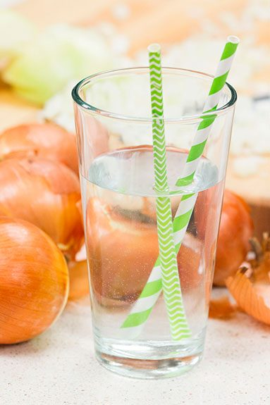 a glass of water with a green striped straw sitting in front of several onions