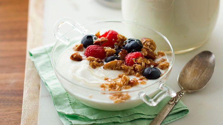 yogurt with granola and berries in a glass bowl sitting on a table next to a spoon and napkin
