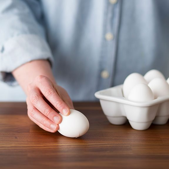 A container of eggs with one removed and being held down by a hand