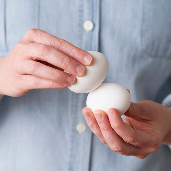 Person holding an egg in each hand and pressing their centers together