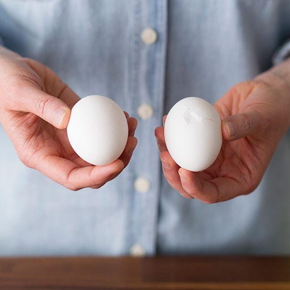Person holding an egg in each hand and presenting them to the viewer to show the growing cracks in their sides