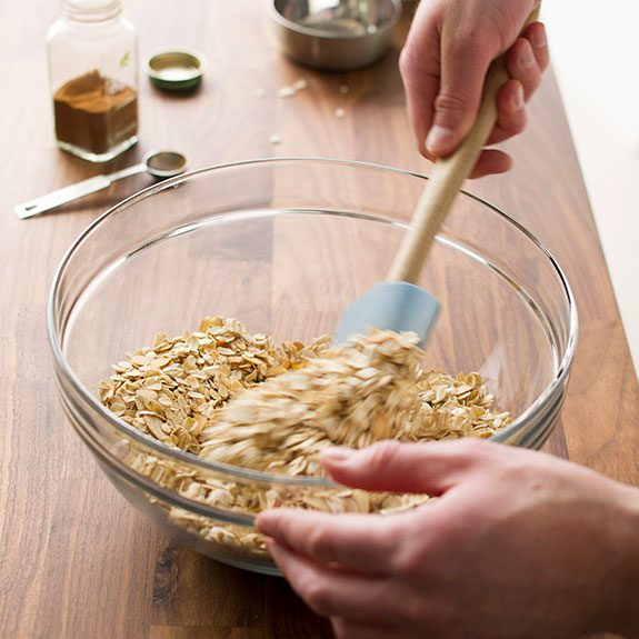 person stirring dry ingredient together in a glass bowl with a spatula