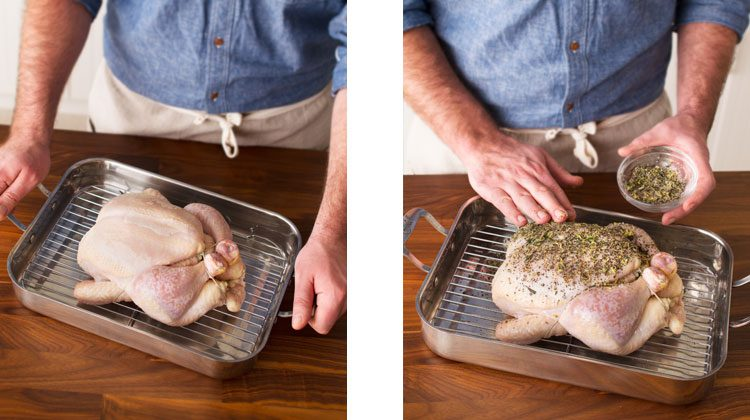 Person holding a shallow pan with a wire rack holding an uncooked chicken. Then, person rubs seasoning liberally over an uncooked chicken
