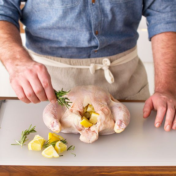 Uncooked chicken being stuffed with rosemary and lemon wedges