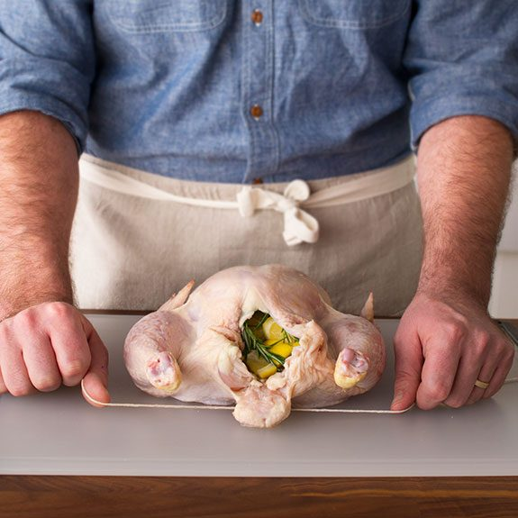 Person holding a string underneath uncooked, stuffed chicken