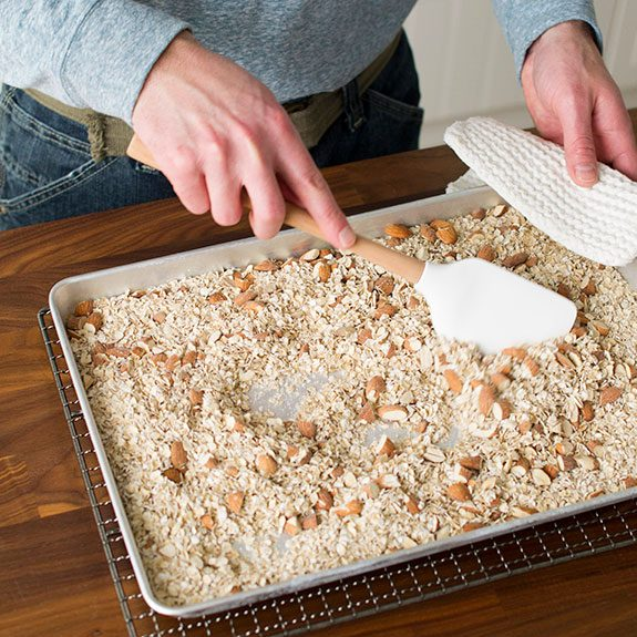 person stirring oats and almonds on a baking sheet with a spatula