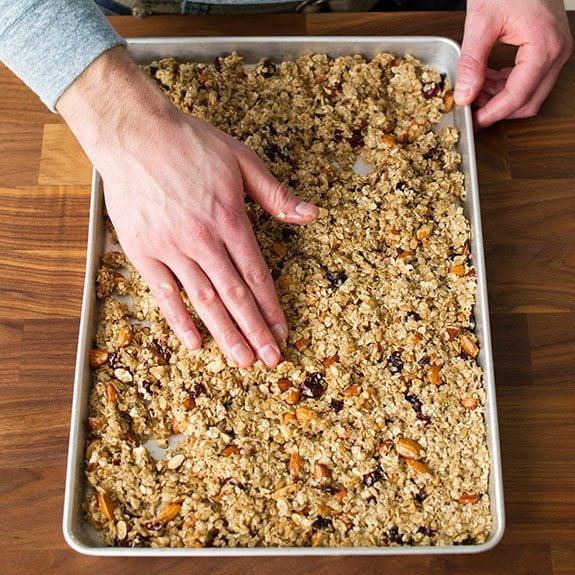 person pressing granola mixture flat onto a baking sheet