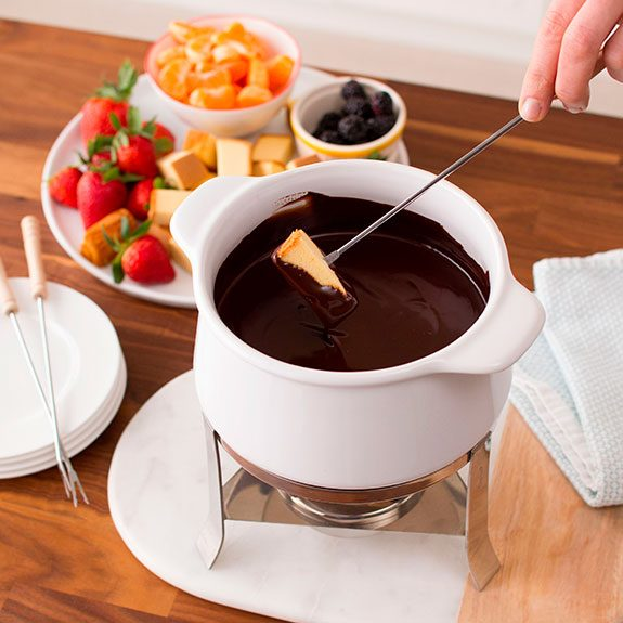 Person dipping cubed angel food cake into a pot filled with hot chocolate fondue and a plate of sliced strawberries and angel food cake pieces sits nearby