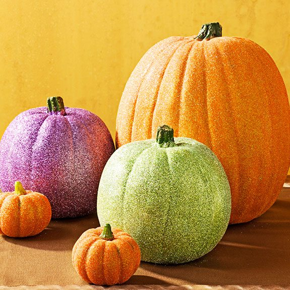 Three glittery pumpkins of different sizes one purple, one green and the final one orange