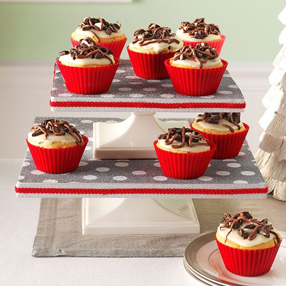 Two cake trays stacked similar to a staircase and decorated with red ribbon on the sides and a grey and white polka dot pattern on the inside. Chocolate cupcakes are scattered across each level