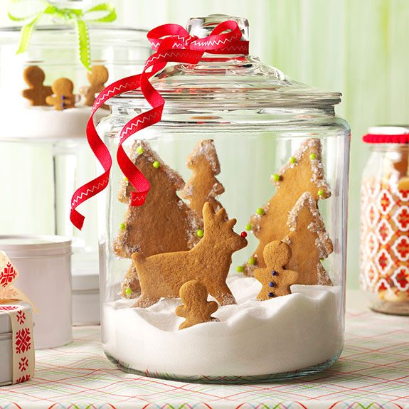 glass jar filled with gingerbread trees and reindeer propped up in a bedding of sugar