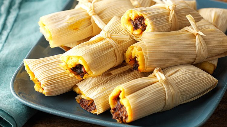 Tamales stacked on top one another on a a blue plate