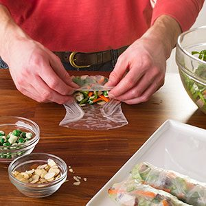 With all the ingredients in place, the rice paper is carefully curled around its fillings