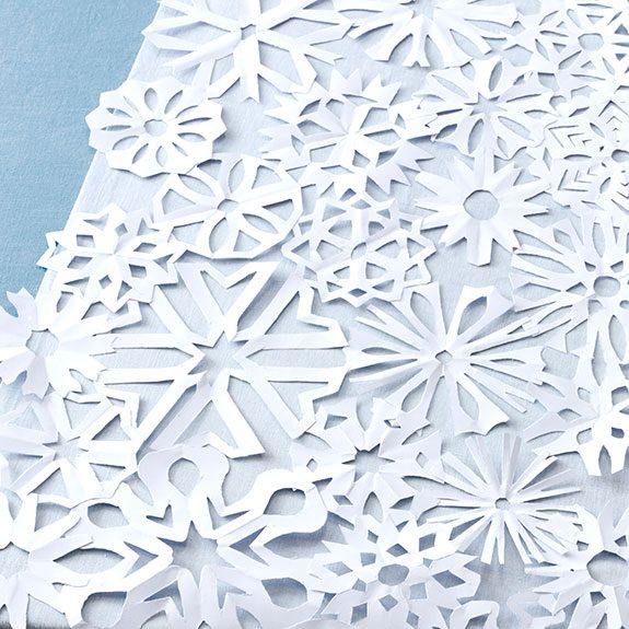Multiple paper snowflakes of varying sizes and cuts taped to a blue table