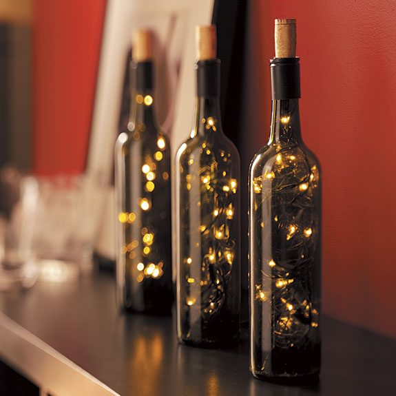 Three corked, green tinted wine bottles sit on a shelf. Each is filled with a small string of lights that create abstract light patterns