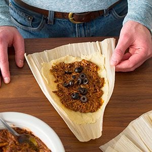 Filling placed in dough inside corn husk and topped with black olives