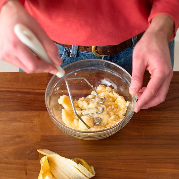 person using a potato masher to mash bananas in a glass bowl