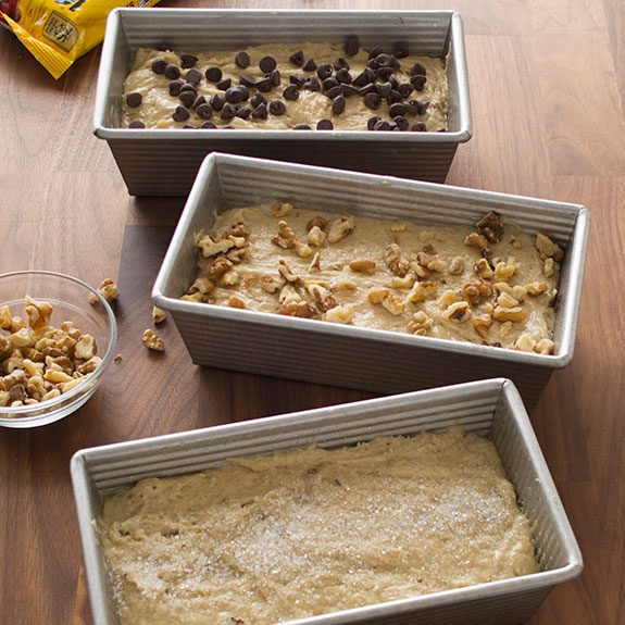 three loaf pans sit together filled with dough and topped with sugar, walnuts and chocolate chips respectively