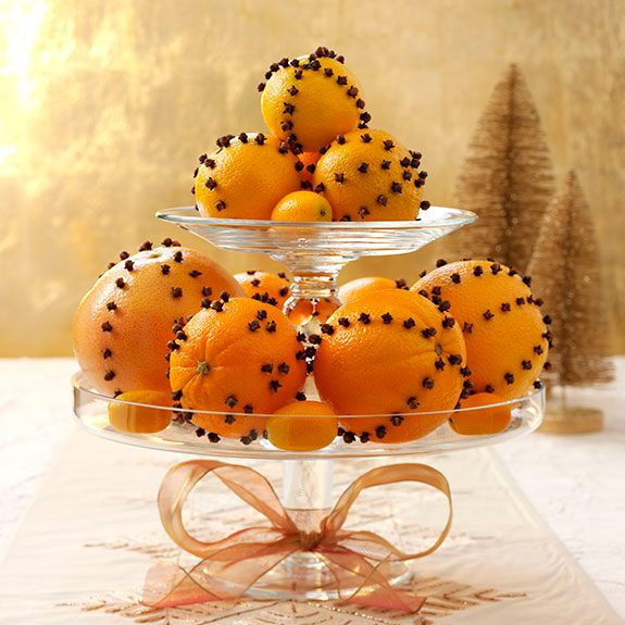 A glass display with two circular levels sports multiple oranges of varying sizes. Each orange is studded with multiple cloves forming lines from the top to bottom