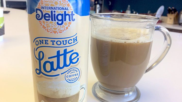 Bottle of International Delight Instant Latte beside a glass cup filled with coffee