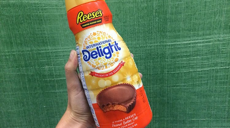 Hand holding a Reese's International Delight creamer with a picture of a Reese peanut butter cup with a bite out of it on the front