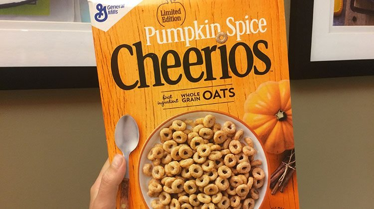 Hand holding up an orange Cheerios box that reads 'Pumpkin Spice Cheerios' a bowl of the cereal is pictured in the middle along with a small pumpkin