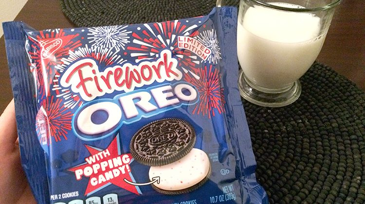 A brand new package of firework oreos beside a glass of milk