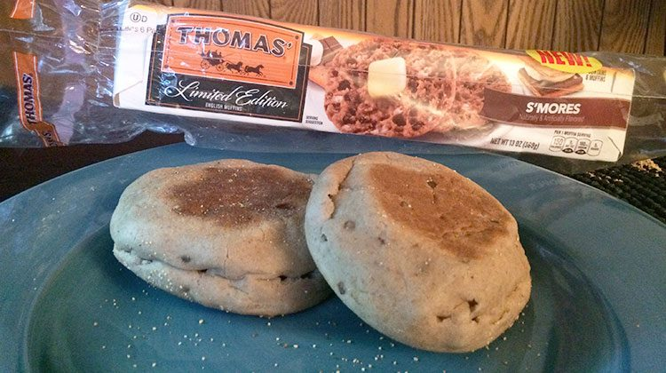 Two S'more's english muffins on a blue plate in front of the Thomas' packaging they came from