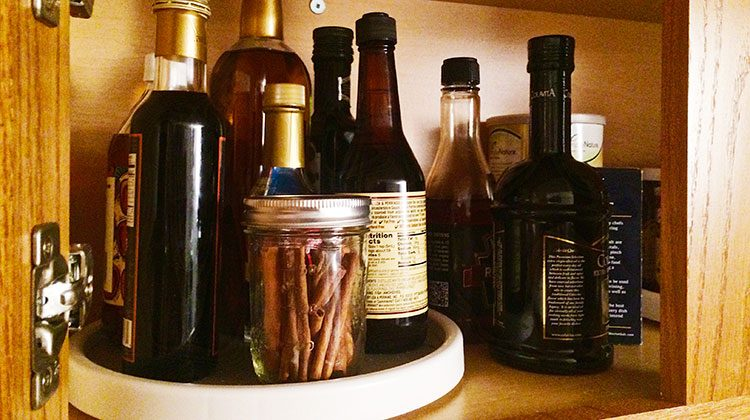 various bottles and containers sitting on a Lazy Susan within a wooden cabinet