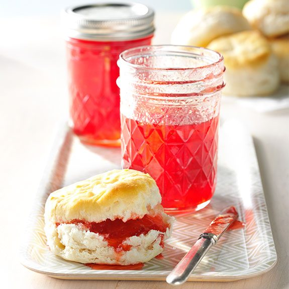 Fresh strawberry freezer jam spread on a homemade biscuit