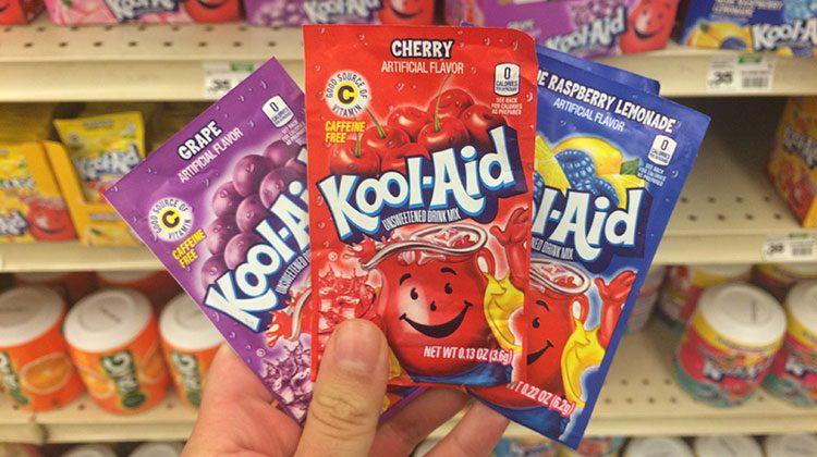 Hand holding three packets of Kool Aid including grape, cherry and blue raspberry lemonade