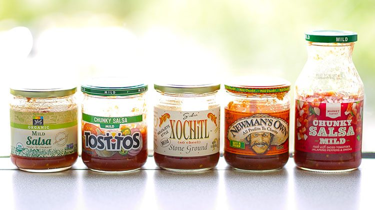 5 different salsa brand jars in a line in front of a window with the sun shining in