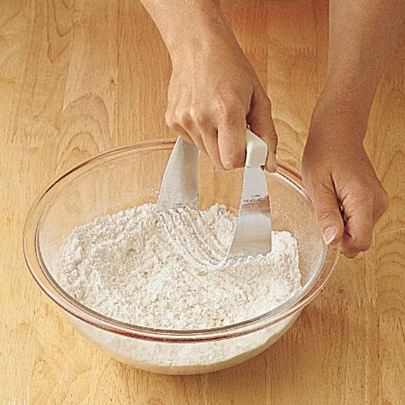 Cutting shortening into biscuit dough with a pastry blender.