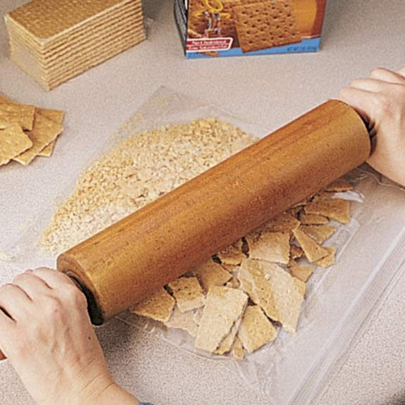 Using a rolling pin to crush graham crackers for a cheesecake crust.