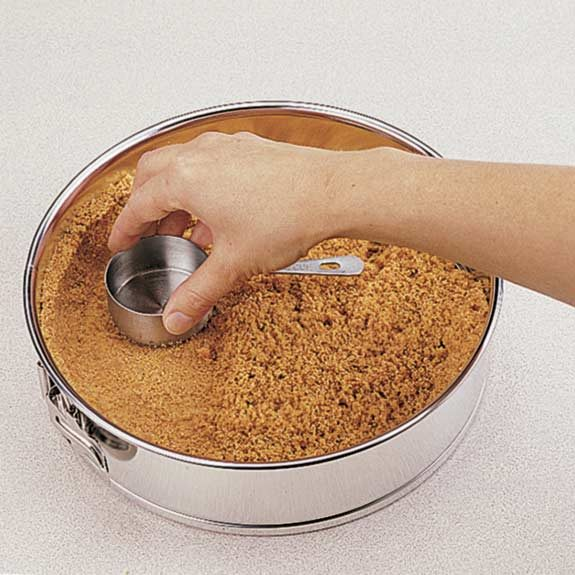 Pressing graham-cracker crust into springform pan with the flat bottom of a measuring cup.