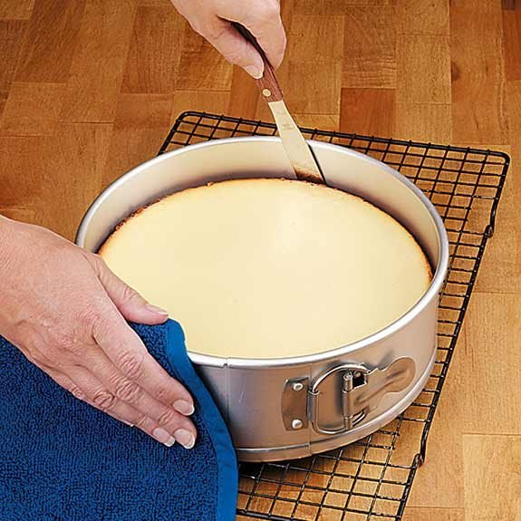 Carefully running a table knife around edges of cheesecake in a springform pan.