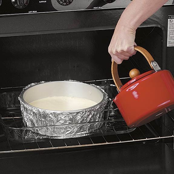 Pouring hot water from a kettle into a baking sheet for a cheesecake water bath.