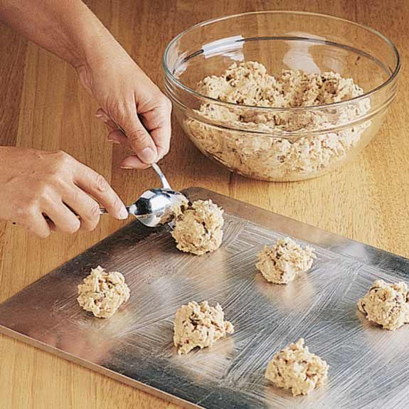Using two spoons to drop chocolate chip cookie dough on a baking sheet.