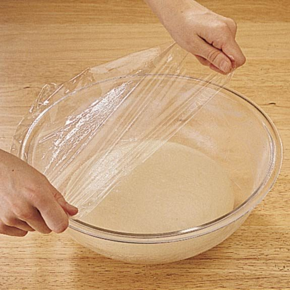 Covering pizza dough with plastic wrap before letting rest for 10 minutes