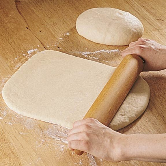 Rolling each half of cinnamon roll dough into a rectangle.