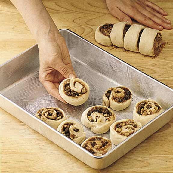 Placing sliced cinnamon rolls cut side down on a greased baking sheet.