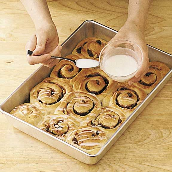 Drizzling glaze over warm cinnamon rolls.