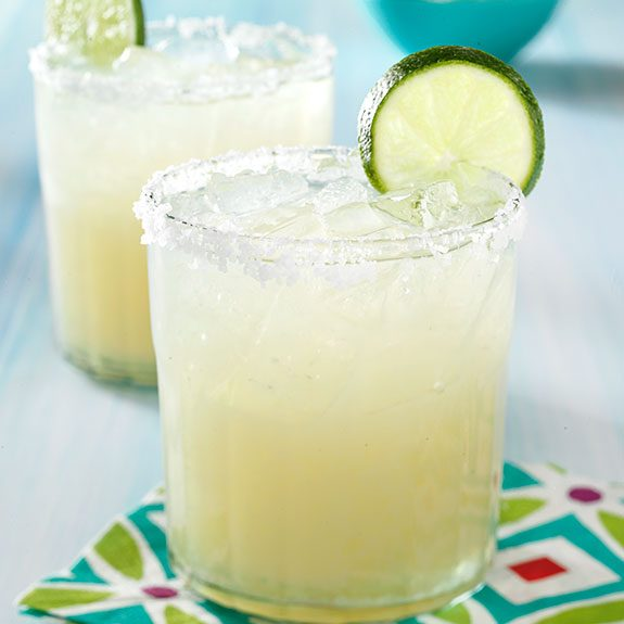 Fresh homemade lime margaritas on the rocks with lime wedges.