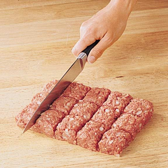Shaping meat mixture into a rectangle to cut into uniform squares for meatballs.